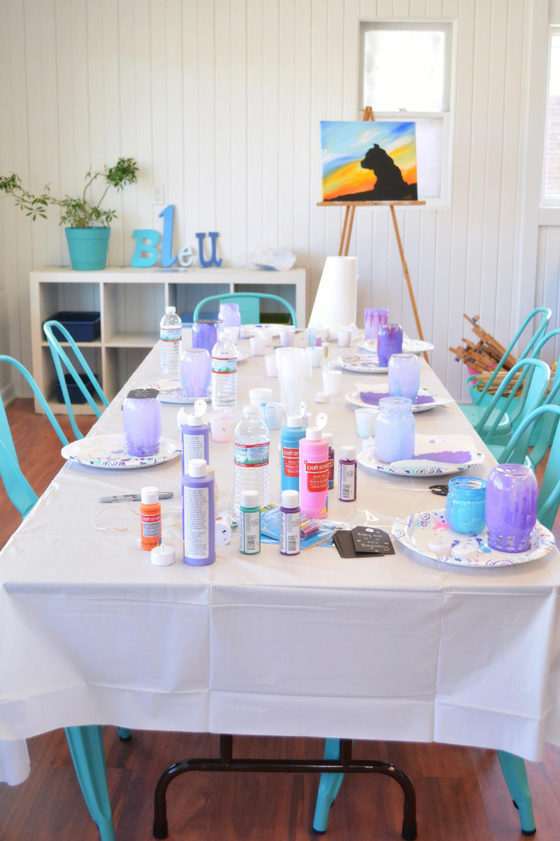 a table set with art supplies ready for a party