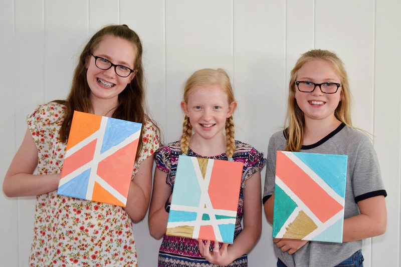 three girls holding paintings